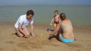 Happy family of three on the beach. Mother and father making sand castle, their son bringing water