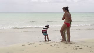 Happy family standing on the beach, slow motion shot at 240fps