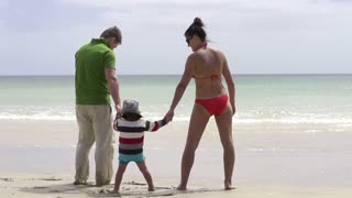 Happy family standing on the beach, slow motion shot at 60fps