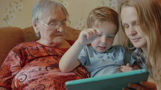 Happy family use tablet sitting on the sofa at home, little boy kisses her grandmother and mother, mother kisses son in return