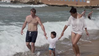 Happy family walking on the beach, slow motion shot at 240fps