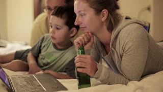 Happy family watching something on laptop in bedroom