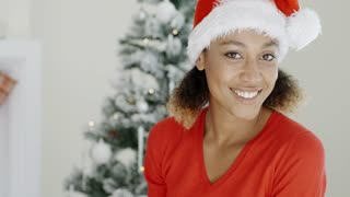 Happy festive young woman in a Santa hat