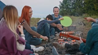Happy friends cooking bbq near campfire and plays guitar outdoor