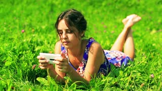Happy girl in blue dress lying on green meadow and typing on cellphone
