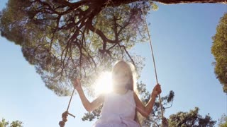 Happy girl in white dress with blond hair with sunglasses on a swing. She is happy and laughing at camera