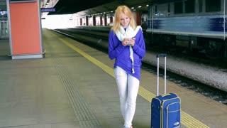 Happy girl standing on platform and tweeting on smartphone
