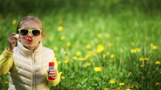 Happy laughing little girl in a meadow blowing soap bubbles