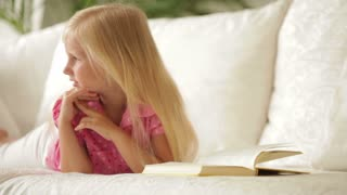 Happy little girl lying on sofa with book and smiling at camera