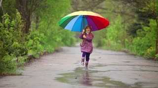 Happy little girl with umbrella running along the path in the park