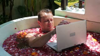 Happy man lying in the bath and working on laptop