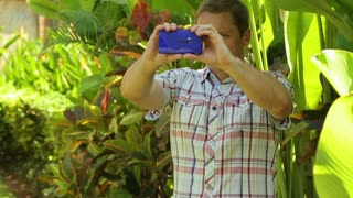 Happy man recording film in the garden on smartphone