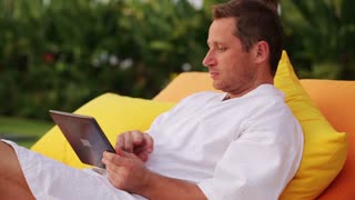 Happy man using tablet in bed and resting