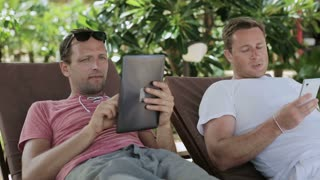 Happy men lying on sunbeds and using modern technology, steadycam shot