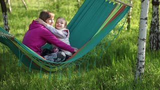Happy mother and daughter hugging and sitting in a hammock outdoor