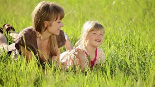 Happy mother and daughter in the grass. Family in  grass
