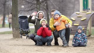 Happy mother, father and their three children waving with the hands. Playground, trees and baby carriage in background.