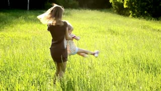Happy mother turns a child in the meadow