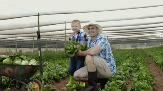Happy portrait of father and son in lettuce filed on their farm.