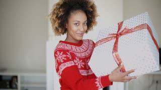 Happy Smiling Girl With Afro Haircut Holding Gift