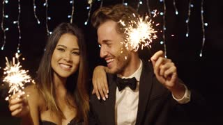 Happy stylish elegant young couple welcoming in the New Year with sparklers looking at the camera with warm friendly smiles against winkling party lights