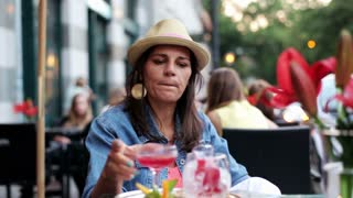 Happy woman drinking cocktail at cafe outside