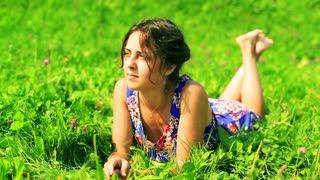Happy woman lying on grass with flowers and relaxing