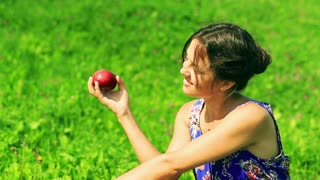 Happy woman sitting on the meadow and eating apple
