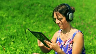 Happy woman sitting on the meadow and listening music on tablet
