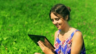 Happy woman sitting on the meadow and using tablet