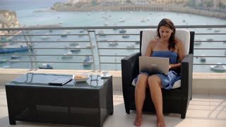 Happy woman sitting on the terrace and finish working on laptop computer