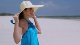 Happy woman standing on windy beach and holding hat, steadycam shot
