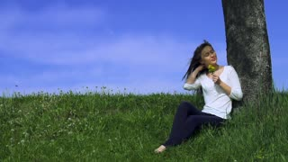 Happy woman styles her hair with fingers and playing with it outdoors in sunny spring or summer. Slow motion 240fps. HD 1920X1080.