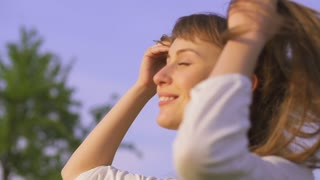 Happy woman walking and styling her hair with fingers outdoors in sunny spring or summer. Dolly shot. Slow motion 240fps. HD 1920X1080.