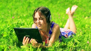 Happy woman watching something on tablet and smiling to the camera on the meadow