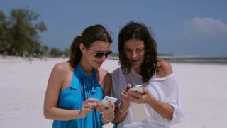 Happy women using cellphones on the beach