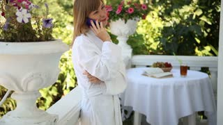 Happy young adult talking on the phone and smiling at the camera
