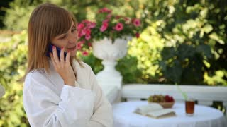 Happy young adult woman talking on the phone and laughing at the camera