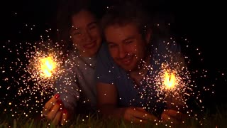 Happy young couple holding burning sparklers at night. Super slow motion 500 fps