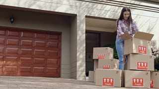 Happy young couple moving/ sorting their boxes while moving into a new house.