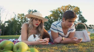 Happy young couple using smartphones on picnic resting with dog and rabbit