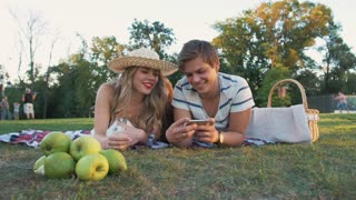 Happy young couple watching smartphone on picnic resting with dog and rabbit