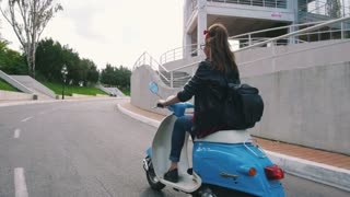Happy young hipster woman in glasses driving a vintage scooter in city, slow motion