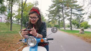 Happy young hipster woman playing smart phone games in park on her vintage scoot