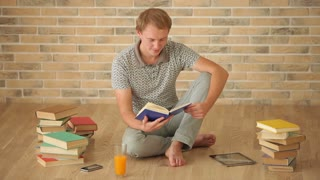 Happy young man sitting on floor reading book looking at camera and smiling