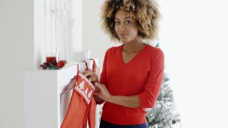 Happy young woman hanging Christmas stockings