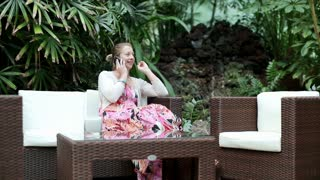 Happy young woman in exotic garden talking on cellphone, steadicam shot