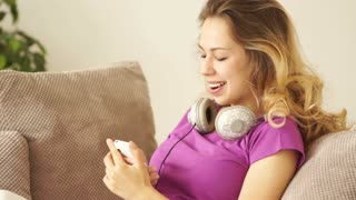 Happy young woman on sofa using mobile phone and smiling