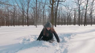 Happy young woman throwing snow up in the air in snow forest, slow motion