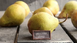 healthy food - tag with an inscription and pears on rural table